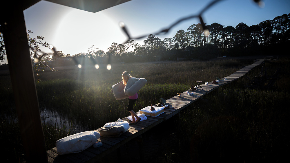 TYBEE ISLAND, GA - FEBRUARY 21, 2018: Tybee Island resident Fran Galloway takes in seat cushions that have been drying on the dock behind her home on Lewis Avenue. Galloway's home, along with most of her neighbors, was damaged by a storm surge from Hurricane Irma that pushed 30 inches of water into their homes on Tybee Island. Less than a year before Hurricane Irma passed the island, Hurricane Matthew caused flooding in the neighborhood. (WABE Photo/Stephen B. Morton)