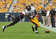 September 01 2012: Iowa Hawkeyes running back Damon Bullock (32) fumbles the ball as he is hit by Northern Illinois Huskies safety Dechane Durante (21) during the first half of the NCAA football game between the Iowa Hawkeyes and the Northern Illinois Huskies at Soldiers Field in Chicago, Illinois on Saturday September 1, 2012. Iowa defeated Northern Illinois 18-17.