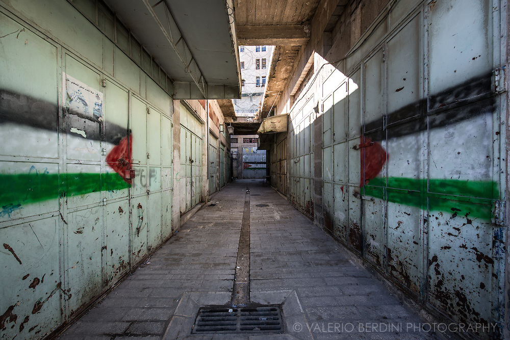 Palestine flags painted on the locked gates of what was the Hebron's gold bazaar. Adjacent to a building occupied by Jewish settlers, seen in the back beyond the barbed wire, all the shops were shut by Israeli army after the second intifada in 2000. They never reopened, leaving families jobless and forcing many to leave.