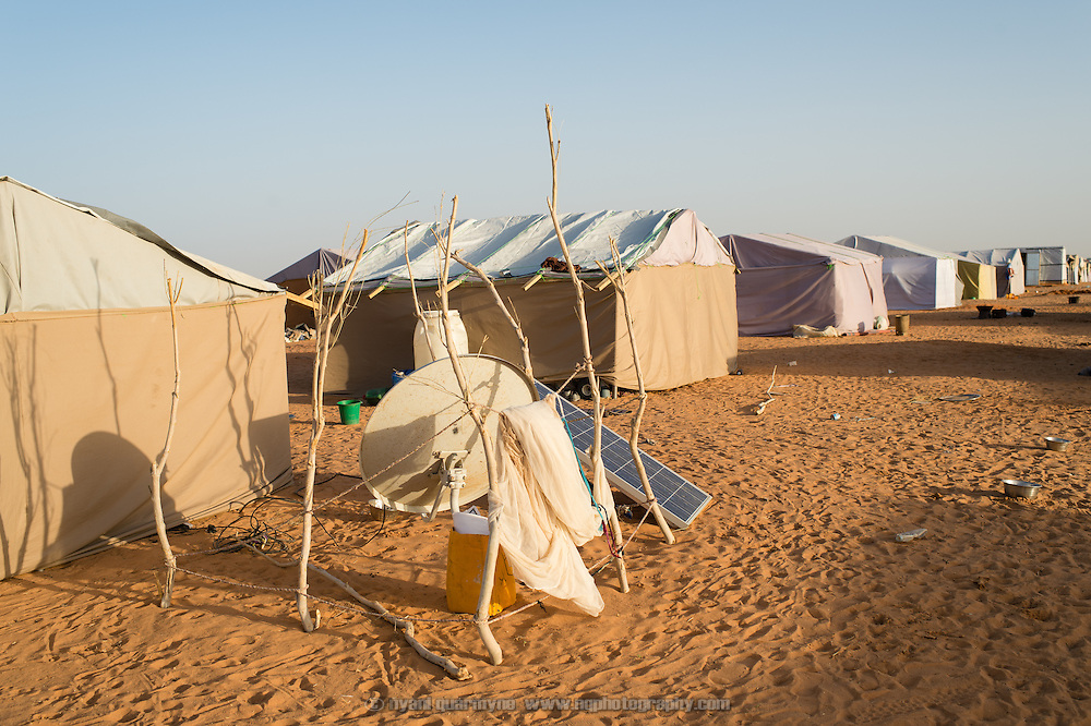 A satellite dish and solar panel, used for luxuries such as a television set, are seen outside a tent in the Mbera refugee camp for Malian refugees in Mauritania on 8 March 2013. Such luxuries are rare - many refugees arrived with nothing more than the clothes on their backs.