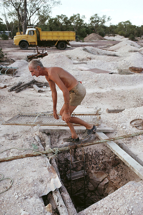 Les Price, opal miner, above mineshaft with dinosaur footprints at Lightning Ridge, Australia. Dinosaur footprints are preserved when the damp surface material (clay or sand) is baked for a long period by the Sun, as at the beginning of a drought. When the overlying water eventually returns, it carries sediments which fill in the footprints, but which are of a different composition to the underlying rock. Here, the excavation of the mine has removed this lower layer (the original 'surface'), leaving the cast of the footprint visible, although it is debatable whether the miner's tools shaped the rock into the shape of a footprint. MODEL RELEASED [1989]
