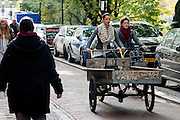 In Utrecht fiets een vrouw met een grote bakfiets over de Oudegracht terwijl een andere vrouw op de fiets haar in wil halen.<br /> <br /> In Utrecht a woman is cycling with a big cargo bike at the Oudegracht while another woman is trying to pass her on the bicycle.