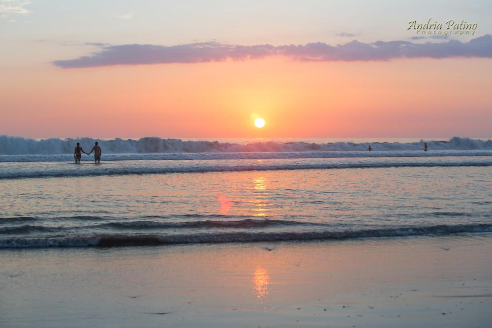 Couple enjoying the sunset on Santa Teresa Beach, Costa Rica