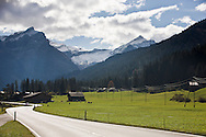 A car travels on a curvy Swiss valley road bordering a cow pasture and with snow covered mountains in the background.