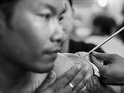 "07 MARCH 2015 - NAKHON CHAI SI, NAKHON PATHOM, THAILAND: A man gets a spiritual tattoo at the Wat Bang Phra tattoo festival. Wat Bang Phra is the best known ""Sak Yant"" tattoo temple in Thailand. It's located in Nakhon Pathom province, about 40 miles from Bangkok. The tattoos are given with hollow stainless steel needles and are thought to possess magical powers of protection. The tattoos, which are given by Buddhist monks, are popular with soldiers, policeman and gangsters, people who generally live in harm's way. The tattoo must be activated to remain powerful and the annual Wai Khru Ceremony (tattoo festival) at the temple draws thousands of devotees who come to the temple to activate or renew the tattoos. People go into trance like states and then assume the personality of their tattoo, so people with tiger tattoos assume the personality of a tiger, people with monkey tattoos take on the personality of a monkey and so on. In recent years the tattoo festival has become popular with tourists who make the trip to Nakorn Pathom province to see a side of ""exotic"" Thailand.   PHOTO BY JACK KURTZ"