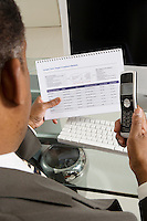 Businessman with Investment Brochure and Cell Phone