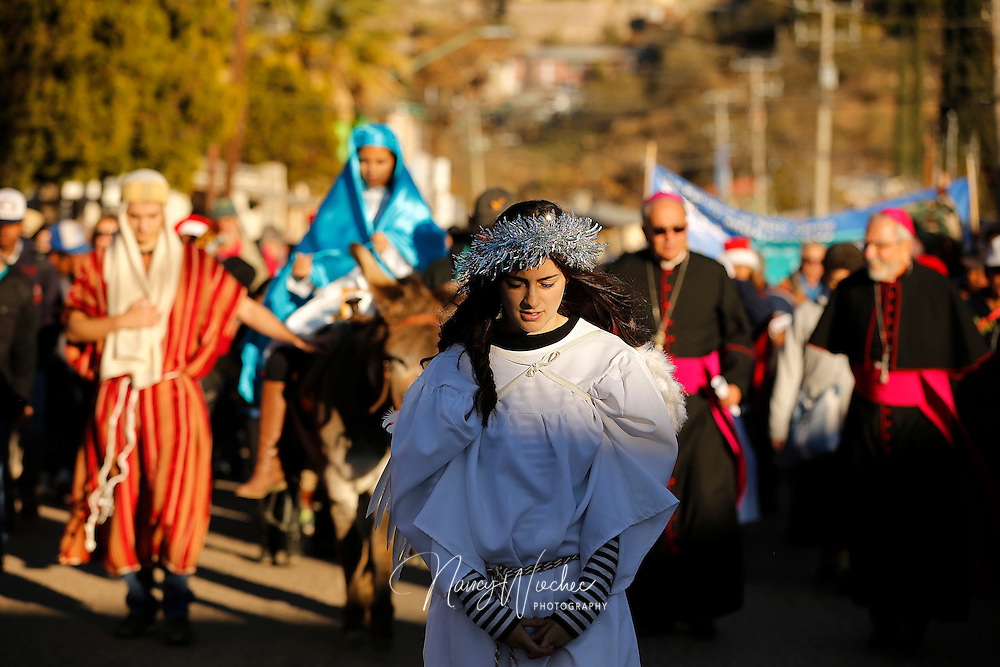 "Dressed as an angel, Zuhaila Parra leads a procession along a street in Nogales, Sonora, Dec. 20. Students from Salpointe and Lourdes Catholic high schools in Nogales, Arizona, took part in the bi-national ""posada"" recalling Mary and Joseph's search for shelter before the birth of Christ. The annual event held by the Kino Border Initiative and Dioceses Without Borders reflected on the struggles of migrants and migrant families. (CNS photo/Nancy Wiechec)"