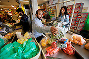 The Qureshi family of Lorenskog, Norway, an Oslo suburb. Pritpal Qureshi, 49, paying for fresh produce in an ethnic market in Oslo while buying a week's worth of groceries.