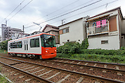 A Toden Arakawa Line tram on tracks near small houses in Tokyo, Japan. Friday, October 12 2012