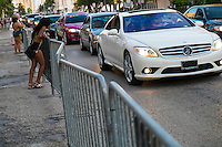MIAMI BEACH - MAY 25: Woman talking in the street with man in car during the Urban Beach Weekend, on May 25, 2013 in Miami Beach. This is the largest Urban Festival in the World, that caters towards the Hip Hop Generation. Over 300.000 participants make the annual trek to South Beach for 4 days full of fun, food, festivities, entertainment, music, and more.
