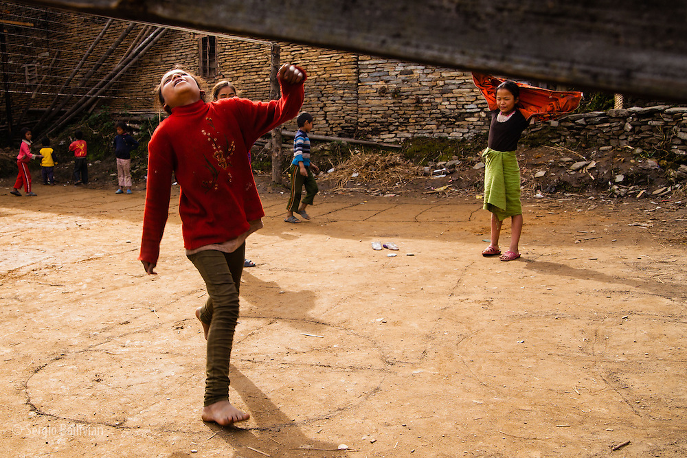 Young kids playing a typical Nepali game called ambret (Nepali hop-scotch) in the village of Gandruk, Nepal.