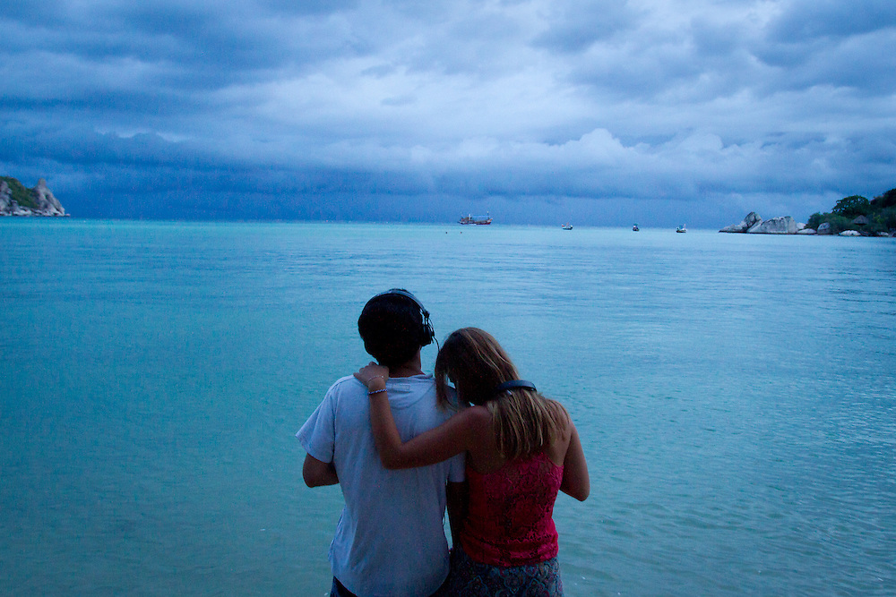 A couple watch as a distant storm rolls in over the warm waters of Koh Tao island, Thailand.