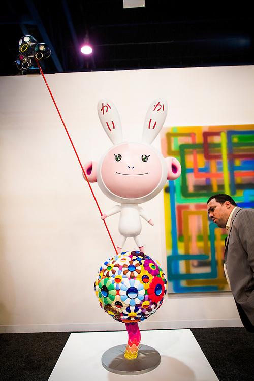An art-lover studies Kaikai Kiki, a  fiberglass sculpture by Takaashi Murakami, at Paris- and Miami-based Galerie Emmanuel Perrotin's space at Art Basel Miami Beach 2007