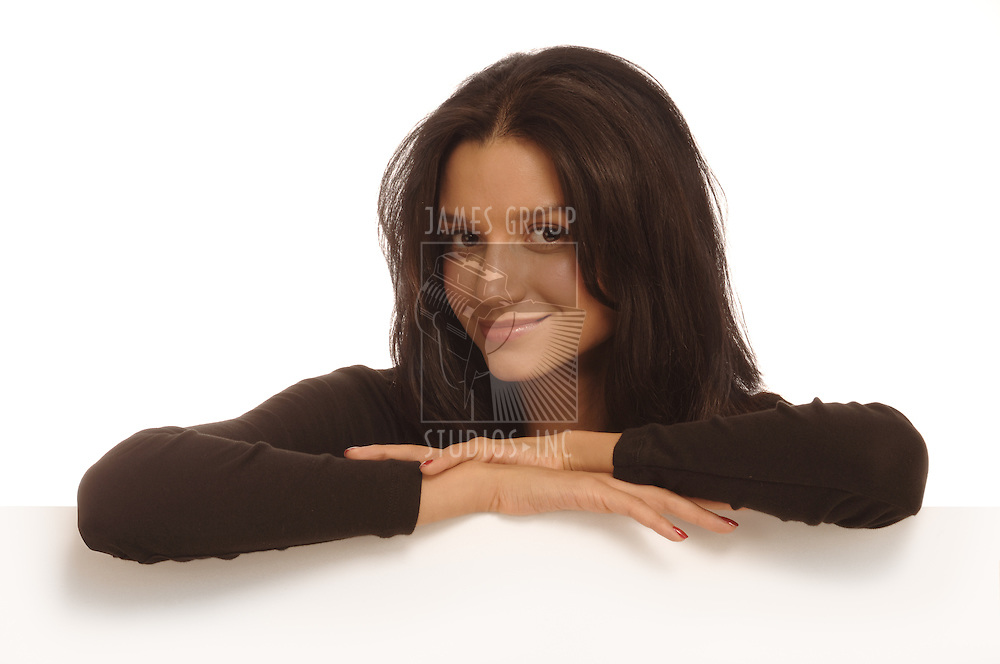 Beautiful young woman behind a white wall resting her arms on the edge looking at the camera