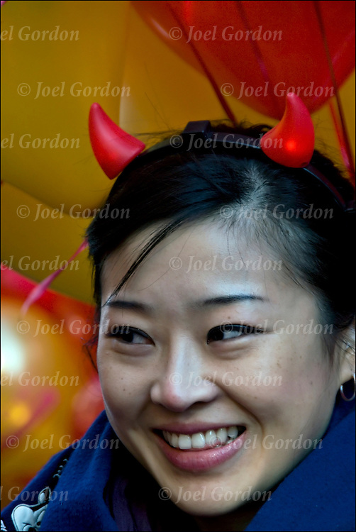 Close up portrait of young Chinese woman with a devilish smile..Ethnic pride and tradition in the Chinese Lunar New Year Celebration in New York Chinatown,The Year of the Ox 4706. Dragon and Lion Dancing.  Two-weekend celabration in the pan-Asian community. The Chinese zodiac sign for the Ox symbolizes prosperity through fortitude and hard work.