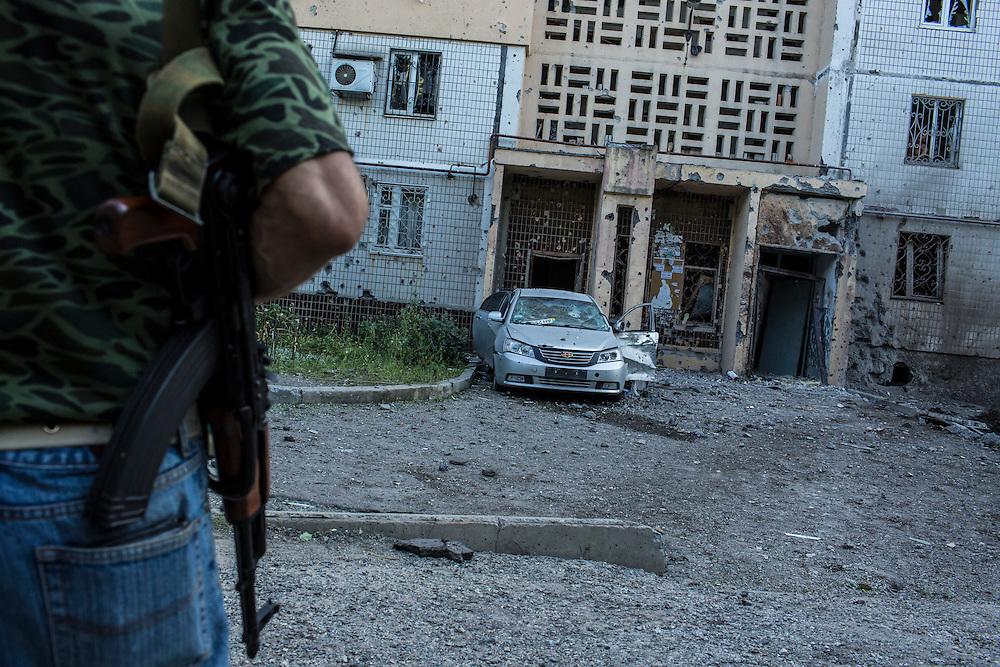 A pro-Russia rebel stands with a gun outside an apartment building hit by a suspected grad rocket strike on Tuesday, July 29, 2014 in Donetsk, Ukraine.