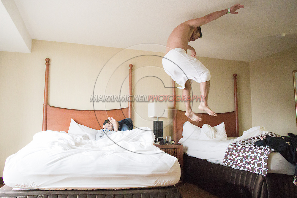"ST. LOUIS, MO, JUNE 19, 2015: Patricio ""Pitbull"" Freire (L) relaxes on his bed while a teammate tests the mattress' firmness  ahead of Bellator 138 in St. Louis, Missouri © Sara Levin"