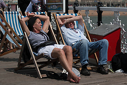 © Licensed to London News Pictures. 01/06/2014. Brighton, UK. A couple relaxes and enjoy the sunshine on Brighton pier. Despite a good start to the weekend on Saturday the up and down weather has deterred some people from coming to the beach. Photo credit : Hugo Michiels/LNP