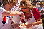 Dignitaries serve birthday cake signifying Saskatoon's 100th anniversary, Optimist Centennial Canada Day, Diefenbaker Park, July 1, 2006