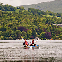 WINDERMERE, UK - JUN 9: Two men kayaking in Windermere on June 9, 2012. Canoeing and Kayaking is one of the most popular activities in the Lake District