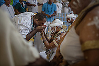 RIO DE JANEIRO, BRAZIL - JANUARY 24: P&atilde;e do Santo, or spiritual father, blesses a newly initiated member during a candomble ceremony, in Rio de Janeiro, Brazil, on Saturday, Jan. 23, 2015. Brazil's Afro-Brazilian religions which in recent years have come under increasing threats and prejudice, particularly from the growing number of evangelical churches. Candombl&eacute; originated in Salvador, Bahia at the beginning of the 19th century when enslaved Africans brought their beliefs with them. Umbanda and candombl&eacute; are Afro-Brazilian religions practiced in mostly Brazil. <br /> (Lianne Milton for the Washington Post)