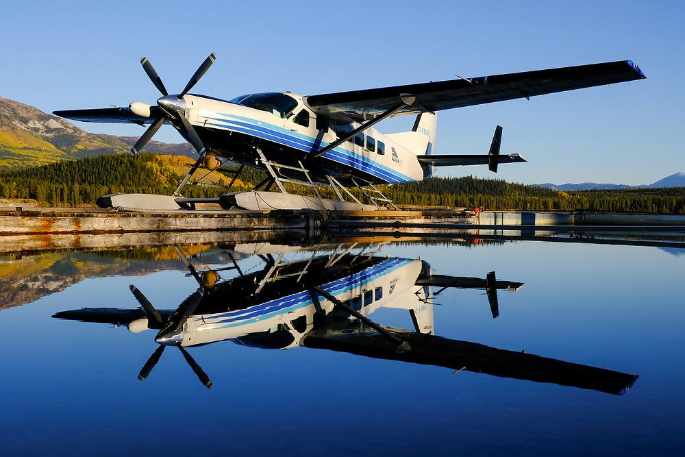 Evening light and still water combine to reflect this Alkan Air Ltd. Cessna 208 Supervan 900 on Schwatka Lake, Yukon