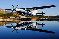 Evening light and still water combine to reflect this Alkan Air Ltd. Cessna 208 Supervan 900 on Schwatka Lake, Yukon