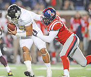 Ole Miss Rebels defensive end C.J. Johnson (10) sacks Mississippi State Bulldogs quarterback Dak Prescott (15) at Vaught-Hemingway Stadium in Oxford, Miss. on Saturday, November 29, 2014. Ole Miss won 31-17.