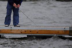 Man in denim slacks and a fleece sweatshirt fishing in choppy waters from a boat dock