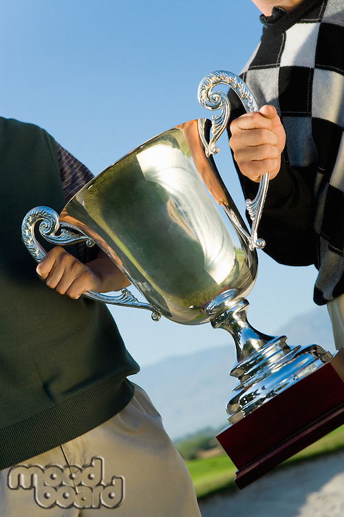 Men Holding Golf Trophy