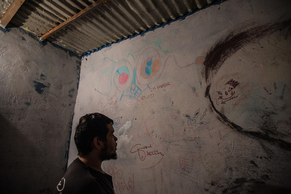 MARACAY, VENEZUELA - JULY 4, 2016: Schizophrenic patient, Accel Simione shows visitors the dozens of original hip hop songs that he has written on the walls of his bedroom. The economic crisis that has left Venezuela with little hard currency has already hit its health system, leaving hospitals without antibiotics, surgeons without gloves and patients dying on emergency room tables.  But beyond the hospital wards, thousands more mental health patients—many of whom had been living relatively normal lives at home with their families under medication—are slipping back into relapse for lack of basic psychiatric medications which control their symptoms, medical experts say. Accel  hears voices that urge him to commit violent acts. After three weeks without olanzapine, a drug used to control his paranoia, the voices inside Accel's head ordered him to kill his brother Gerardo.  When he refused, they ordered him to cut off his arm, and so he attacked himself. He took an electric circular saw from the family's garage, switched it on and began slicing into his arm. Soon his father found him and wrested the tool from his son's bloody hands. PHOTO: Meridith Kohut for The New York Times