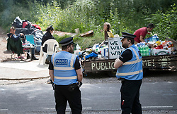 © Licensed to London News Pictures. 23/06/2017. Dorking, UK. Police watch over the remaining environmental protestors who have moved their camp over the road after being evicted. Workers are dismantling a protest fort built over an oil well site near Leith Hill in the North Downs . Protestors have been evicted from the camp over the last few days. Planning permission for 18 weeks of exploratory drilling was granted to Europa Oil and Gas in August 2015 after a four-year planning battle. The camp was set up by protestors in October 2016 in order to draw attention to plans to drill in this Area of Outstanding Natural Beauty (AONB) in the Surrey Hills. The camp has received support from the local community. Photo credit: Peter Macdiarmid/LNP