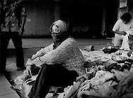 Woman, who has sought refuge with hundreds of other displaced local villagers at Maguwoharjo Stadium in Sleman by the Mt. Merapi's worst eruption in over 100 years, seems lost in tired thought while another displaced woman sifts through donated clothing.  Sleman, Java, Indonesia..