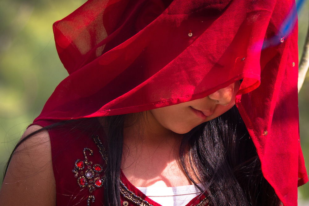 A hindu girl with a red veil attends a prayer meeting at the temple of Dakshinkali, Nepal.