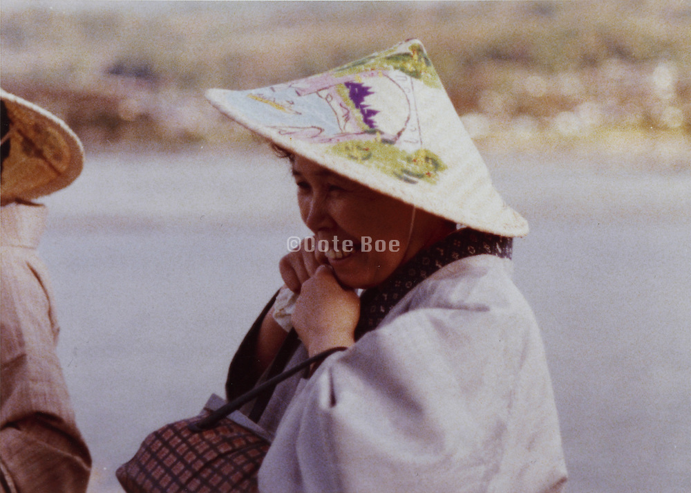 tourist putting on the traditional hat for a river boat trip Japan 1970s