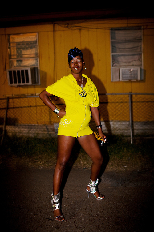 A young woman strikes a pose, showing off her outfit, in the Baptist Town neighborhood of Greenwood, Mississippi before going out clubbing on September 25, 2010.