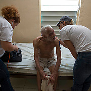 Comerio, PR, November 11, 2017--Dr. Lourdes Marrero, left, and internist Paula Jeffs, with Mission de Haiti Se Pone de Pie check on  94-year-old  Pedro Andino in his home in La Verde, PR. Medical teams made house visits in Comerio and surrounding neighborhoods to check on the elderly and sick.  Photo by Lori Waselchuk/BAF
