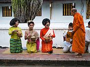 "11 MARCH 2016 - LUANG PRABANG, LAOS:  Lao women wait to present monks with alms during the tak bat in Luang Prabang. Luang Prabang was named a UNESCO World Heritage Site in 1995. The move saved the city's colonial architecture but the explosion of mass tourism has taken a toll on the city's soul. According to one recent study, a small plot of land that sold for $8,000 three years ago now goes for $120,000. Many longtime residents are selling their homes and moving to small developments around the city. The old homes are then converted to guesthouses, restaurants and spas. The city is famous for the morning ""tak bat,"" or monks' morning alms rounds. Every morning hundreds of Buddhist monks come out before dawn and walk in a silent procession through the city accepting alms from residents. Now, most of the people presenting alms to the monks are tourists, since so many Lao people have moved outside of the city center. About 50,000 people are thought to live in the Luang Prabang area, the city received more than 530,000 tourists in 2014.      PHOTO BY JACK KURTZ"