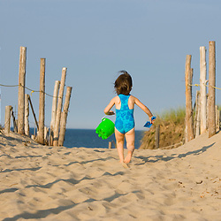 A young girl (age 4) heads to the beach at the Cape Cod National Seashore in Truro, Massachusetts.  Head of the Meadow Beach.