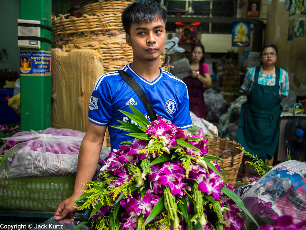 21 OCTOBER 2014 - BANGKOK, THAILAND: A flower vendor in the Bangkok Flower Market. The Bangkok Flower Market (Pak Klong Talad) is the biggest wholesale and retail fresh flower market in Bangkok. It is also one of the largest fresh fruit and produce markets in the city. The market is located in the old part of the city, south of Wat Po (Temple of the Reclining Buddha) and the Grand Palace.    PHOTO BY JACK KURTZ