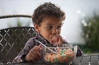 Pensive little boy looking away with cereal bowl on table