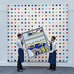 "© Licensed to London News Pictures. 23/06/2017. London, UK. Technicians show ""Two Paintings with Dado"", 1983, by Roy Lichtenstein (estimate GBP2.4-3m) in front of ""1-Heptene"", 2004-2011, by Damien Hirst (estimate GBP0.5-0.7m) at the preview of Sotheby's Contemporary Art Sale in New Bond Street.  The auction, which is dominated by Pop art, takes place on 28 June. Photo credit : Stephen Chung/LNP"