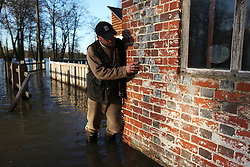 © Licensed to London News Pictures. 29/11/2012. Mapledurham, UK. Miller Corry Starling points at an old flood marker from '76' on Mapledurham Watermill. It is unknown which century this was from as the current structure was built in the 1600's. The watermill is the last commercially working watermill on The River Thames. Photo credit : Rebecca Mckevitt/LNP