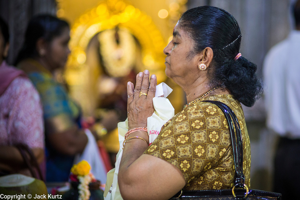 22 DECEMBER 2012 - SINGAPORE, SINGAPORE:   A woman prays in Sri Veeramakaliamman Temple, a Hindu temple located in Little India in the southern part of Singapore. The Sri Veeramakaliamman Temple is dedicated to the Hindu goddess Kali, fierce embodiment of Shakti and the god Shiva's wife, Parvati. Kali has always been popular in Bengal, the birthplace of the labourers who built this temple in 1881. Images of Kali within the temple show her wearing a garland of skulls and ripping out the insides of her victims, and Kali sharing more peaceful family moments with her sons Ganesha and Murugan. The building is constructed in the style of South Indian Tamil temples common in Tamil Nadu as opposed to the style of Northeastern Indian Kali temples in Bengal.     PHOTO BY JACK KURTZ
