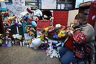 A woman mourns in front of a makeshift memorial following Monday's deadly shooting at the Tim's Market in Corpus Christi. The well-liked store owner was shot and killed during a midday robbery.