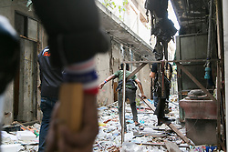 © Licensed to London News Pictures. 17/01/2014. A group of anti-government protestors in an abandoned apartment complex search for a suspect whom threw an explosive device injuring eight people during an anti-government street rally on January 17, 2014 in Bangkok, Thailand. Anti-government protesters launch 'Bangkok Shutdown', blocking major intersections in the heart of the capital, as part of their bid to oust the government of Prime Minister Yingluck Shinawatra ahead of elections scheduled to take place on February 2. Photo credit : Asanka Brendon Ratnayake/LNP