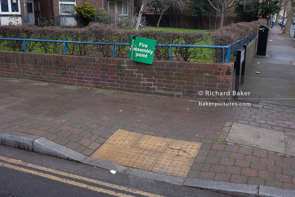 A sign for a Fire Assembly Point for local residents of a tower block, on a street corner near Elephant & Castle, on 4th January, London borough of Southwark, England.
