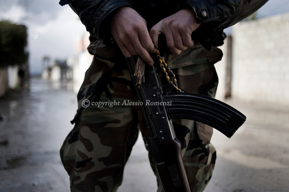 SYRIA - Al Qsair. A member of Free Syrian Army as he holds is AK-47 and his in Al Qsair, on January 27, 2012. Al Qsair is a small town of 40000 inhabitants, located 25Km south-west of Homs. The town is besieged since the beginning of November and so far it counts 65 dead. ALESSIO ROMENZI