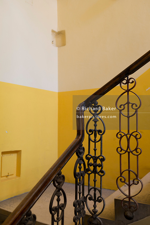 Yellow walls, wooden bannisters and railings in stairwell of a Slovenian building, on 23rd June 2018, in Celje, Slovenia.