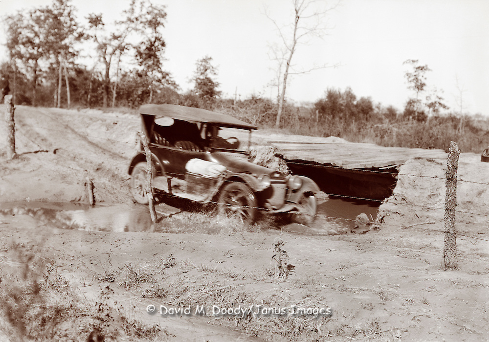 Choice of a bad bridge or a muddy stream crossing in a vintage auto. Auto going through a deep muddy stream bypassing a questionable bridge. A muddy country road with barbed wire along the edge of the road.  vintage photo circa 1910 .